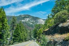 2007年被采取的加利福尼亚1月国家公园美国优胜美地 在森林公路的旅游汽车 向Yometi村庄的路 库存照片
