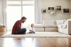 年轻一起使用在他们的客厅的父亲和儿子 库存图片