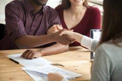 年轻不同种族的夫妇与房地产开发商握手 免版税库存图片