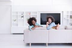 年轻不同种族的夫妇在客厅 库存照片