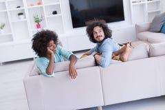 年轻不同种族的夫妇在客厅 免版税库存图片