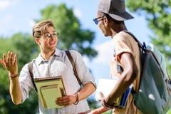 年轻不同种族的学生拿着书和谈话在公园 免版税库存图片
