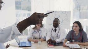 年轻不同种族的实习生听的演讲美国黑人的医生在诊所的医疗会议 在的演讲期间 影视素材
