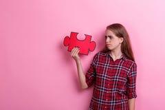 年轻不悦的女孩、举行一个大难题和看看它 在桃红色背景 免版税图库摄影