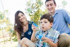 年轻与他的父母的男孩吹的泡影在公园 免版税库存图片