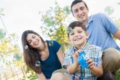 年轻与他的父母的男孩吹的泡影在公园 库存图片