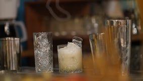 年轻专业侍酒者倾吐的白色crem饮料到玻璃里有很多冰和把腌汁放在它上 影视素材
