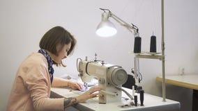 年轻专业裁缝是在运作的过程中,缝合衣裳,使用缝纫机,并且布料,切除了螺纹与 股票录像