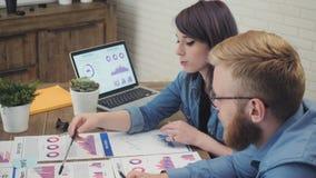 年轻业务经理在办公室分析文件,新的起始的项目的计划 股票视频