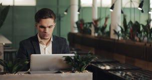 年轻严肃的商人坐在舒适咖啡馆和与膝上型计算机一起使用 研究项目的自由职业者或学生或 影视素材
