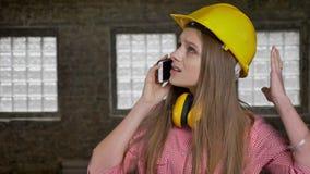 年轻严肃的女孩建造者在电话谈话,观看上面,通信构想 影视素材