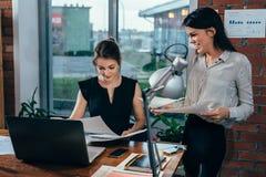 年轻个人助手谈论计划与上司在她的办公室 免版税库存照片