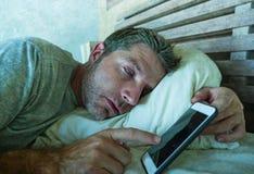 年轻互联网上瘾者人睡觉在家庭长沙发的拿着手机在他的在智能手机的手上和社会媒介过度使用和onlin 免版税库存照片