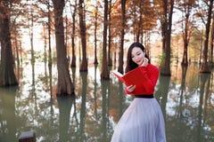 年轻亚洲中国妇女读书在秋天水红色森林里 库存图片