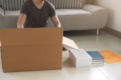 年轻亚洲人包装和投入材料在大纸板箱f 免版税库存照片
