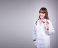年轻亚洲医生立场在她的手上的拿着红色心脏 免版税库存照片
