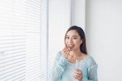 年轻亚洲吃药片和饮用水的秀丽少妇 免版税库存照片