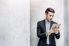 年轻亚洲和现代有吸引力的商人读书或工作 库存图片