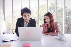 年轻亚洲商人与膝上型计算机一起使用在办公室 免版税库存图片