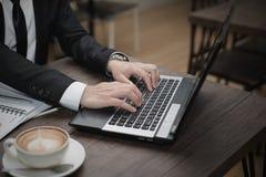年轻亚洲商人与膝上型计算机一起使用 免版税库存照片