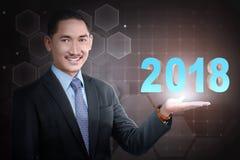 年轻亚洲商人在他的手上的举行2018个数字 免版税库存图片