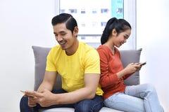年轻亚洲夫妇坐有手机的沙发 免版税库存照片