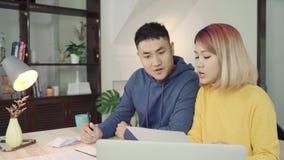 年轻亚洲夫妇处理的财务,回顾他们的银行帐户使用便携式计算机和计算器在现代家 影视素材