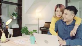 年轻亚洲夫妇处理的财务,回顾他们的银行帐户使用便携式计算机和计算器在现代家 股票视频