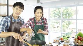 年轻亚洲夫妇是愉快一起烹调在度假 免版税图库摄影