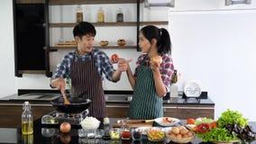 年轻亚洲夫妇是愉快一起烹调,两个家庭互相帮助准备在厨房里烹调 免版税库存图片