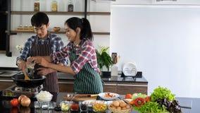 年轻亚洲夫妇是愉快一起烹调,并且帮助烹调食物早晨 免版税库存图片