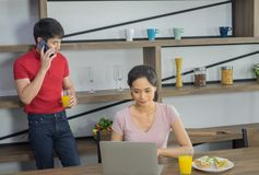 年轻亚洲夫妇,焦点对妇女看计算机膝上型计算机 免版税库存照片