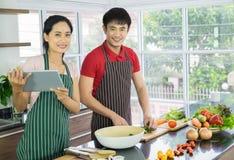 年轻亚洲夫妇 烹调在厨房里的站立的微笑 愉快地一起沙拉为食物做准备 免版税图库摄影