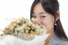 年轻亚洲女孩面孔愉快地微笑着手中藏品眉头 免版税库存照片