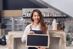 年轻亚洲女性barista在牛仔布围裙举行有美好的微笑的一个黑板在她自己的咖啡店欢迎 图库摄影