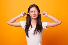 年轻亚洲妇女块有手指的两个耳朵 库存图片