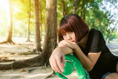 年轻亚洲妇女室外坐公开长凳和说谎沿长凳在公园在温暖的阳光天 免版税库存图片