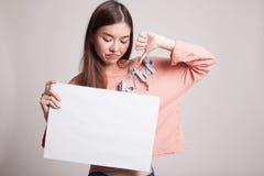 年轻亚洲妇女展示翻阅下来与白色空白的标志 免版税图库摄影