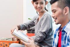 年轻亚洲对新的公寓的夫妇运载的财产 库存图片