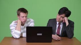 年轻亚洲工作与膝上型计算机一起的商人和年轻斯堪的纳维亚商人 影视素材