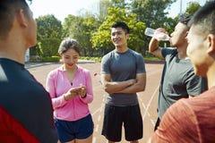 年轻亚洲成人relexing和谈话在轨道 免版税库存照片