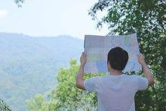 年轻亚洲旅游探索的地图后面看法在绿色新自然背景中的 旅行和冒险概念 库存图片