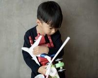 年轻亚洲男孩无罪可爱的使用的玩具 库存照片