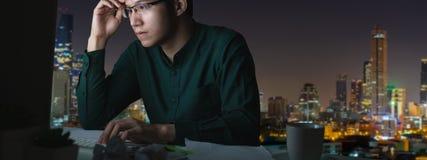 年轻亚裔人横幅坐书桌桌工作晚和坚硬与计算机膝上型计算机在办公室有夜光城市视图 库存图片