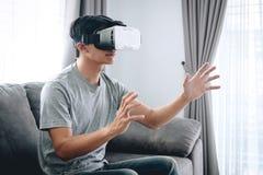 年轻亚裔人获得佩带的乐趣演奏虚拟现实耳机玻璃对在家享用在假日,3D小配件技术, 库存图片