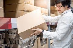 年轻亚裔人运载的纸箱在仓库里 库存照片