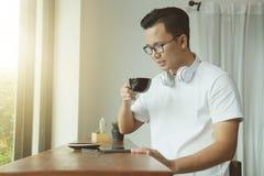 年轻亚裔人饮用的咖啡和使用数字式片剂在coff 免版税库存图片
