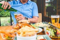 年轻亚裔人饮用的啤酒和愉快eatting的食物,当enjo时 库存照片