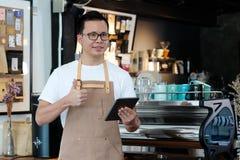 年轻亚裔人, barista,使用在咖啡馆柜台backgroun的片剂 图库摄影