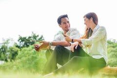 年轻亚裔可爱的夫妇或大学生一起听到歌曲音乐坐智能手机在公园 库存图片